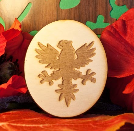 Aquila con artigli sfoderati incisa su ovale in legno